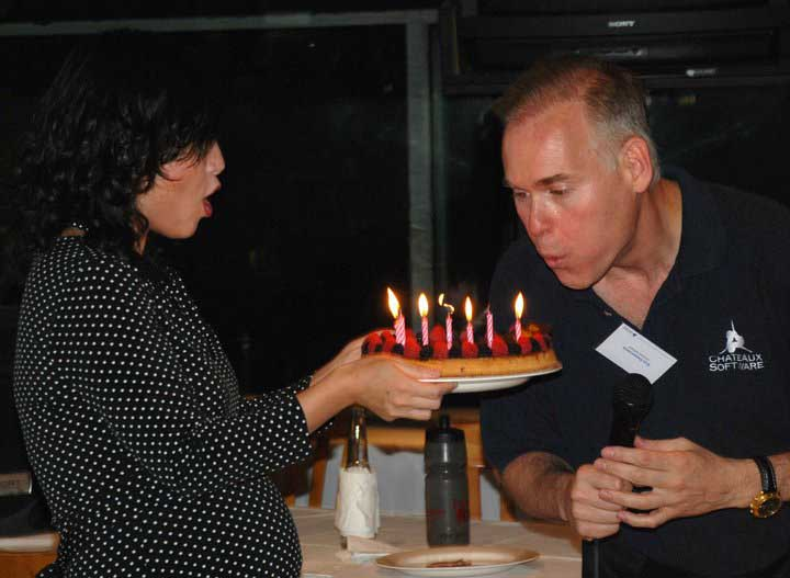 Chateaux owner and CEO Ken Zimmerman blows out birthday candles from a cake held by his wife